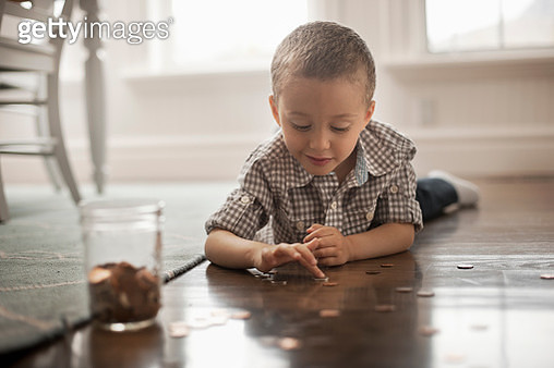 A child lying on his stomach on the floor playing with coins and putting them in a glass jar. - gettyimageskorea