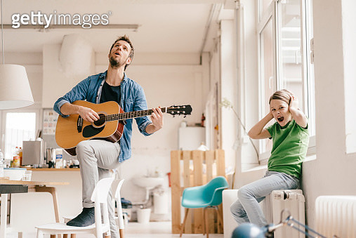 Horrified son covering his ears with father playing guitar at home - gettyimageskorea