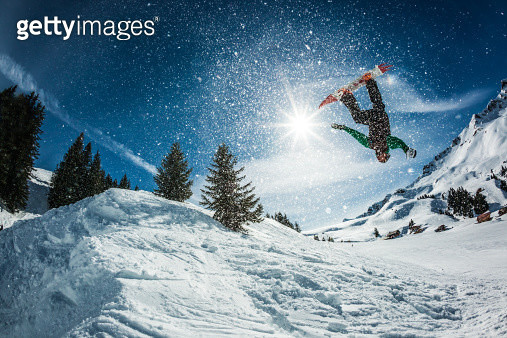 snowboarder doing a backflip with snow exploding - gettyimageskorea