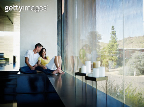 Husband and wife sitting near window of home laughing - gettyimageskorea