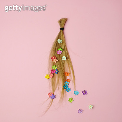 Lock of blonde ponytail with scattered flowers on a pink background. - gettyimageskorea