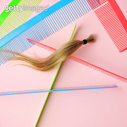 Lock of blond ponytail arranged on pink background with colorful oversized combs. - gettyimageskorea