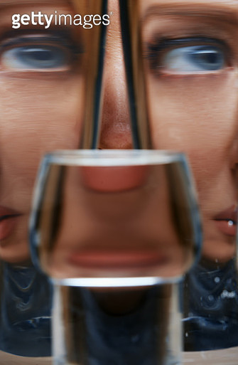 Distorted woman behind the glassware with water - gettyimageskorea