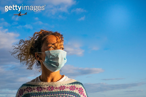 one curly and beautiful woman wearing medical mask to prevent any type of disease or virus like coronavirus or covid-19 - airplane inside of her head at the background like risky vacations hazard - gettyimageskorea