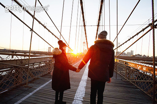 Couple in winter coats and hats holding hands on Brooklyn Bridge at sunset - gettyimageskorea