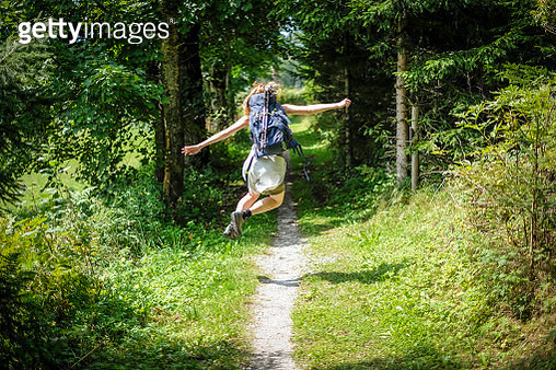 Rear view of woman jumping in forest - gettyimageskorea