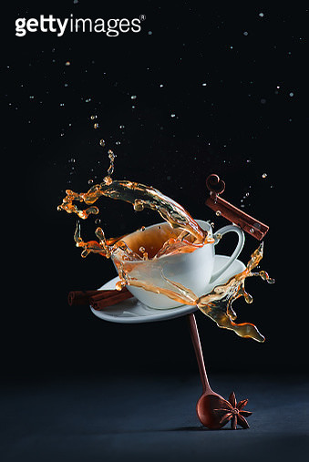 Coffee cup with a splash balancing on a wooden spoon - gettyimageskorea
