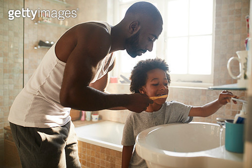 A boy in the bathroom brushing his teeth with his dad in the morning with bamboo toothbrush - gettyimageskorea