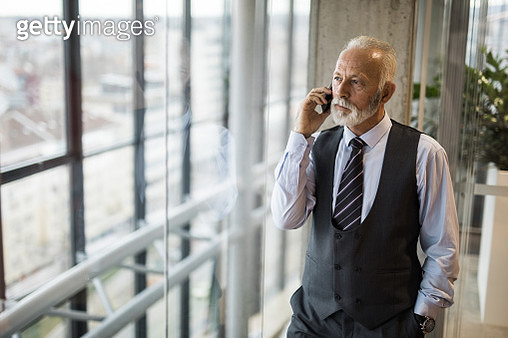 Mature businessman talking on mobile phone by the window. - gettyimageskorea