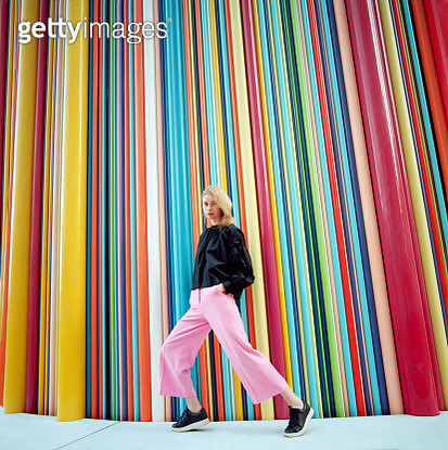 Portrait of young beautiful woman with long blond hair wearing black blouse and pink pants on colorful background. Shot on medium format film camera - gettyimageskorea