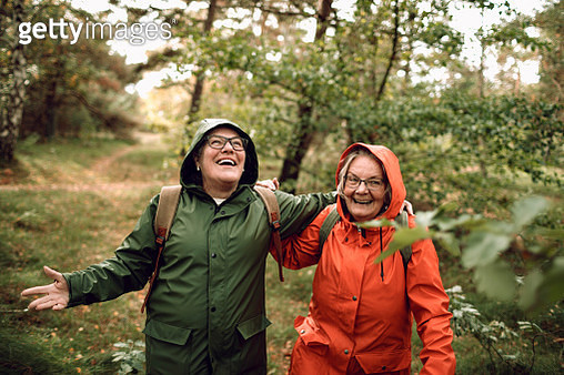 Close up of two female seniors hiking through the forest - gettyimageskorea