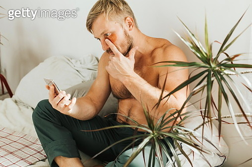 The man is sitting on his bed at home. Cosmetic patches on the face, care for the skin around the eyes. - gettyimageskorea