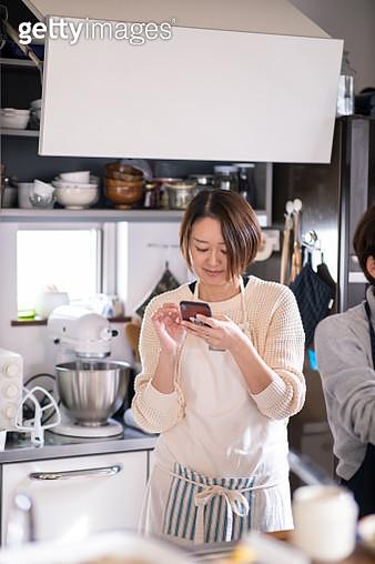 Woman checking recipe on smart phone in domestic kichen wirh friend - gettyimageskorea