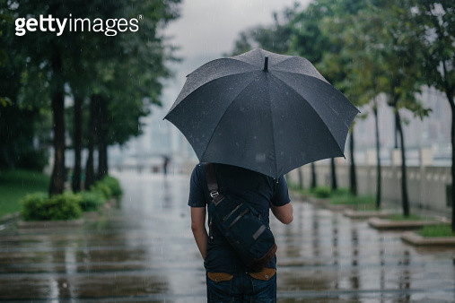 Rear view of male holding umbrella in rainy city - gettyimageskorea