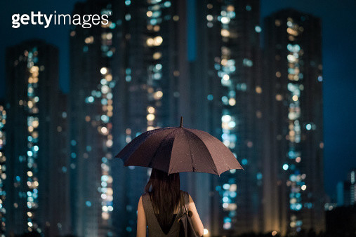 Businesswoman overlooking cityscape on a rainy day - gettyimageskorea