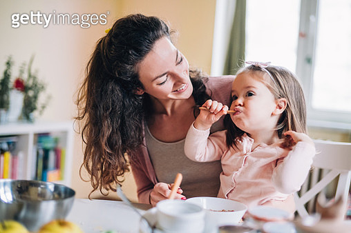 Little girl eat breakfast in bowl with her mother in home - gettyimageskorea