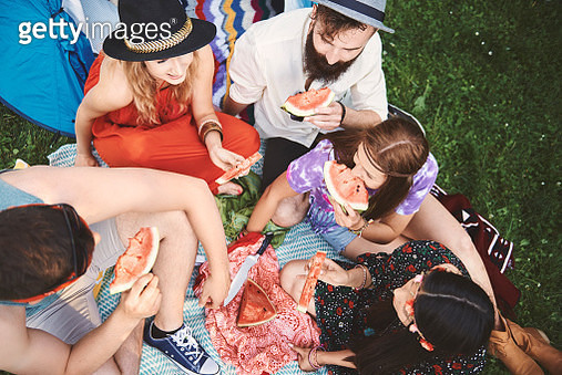 Overhead view of young boho adult friends eating melon slices at festival - gettyimageskorea