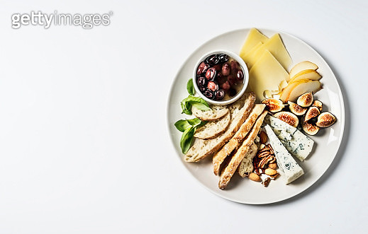 Cheese platter with pears, figs, nuts, bread, olives, and blue cheese on gray background - gettyimageskorea
