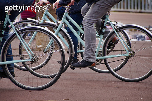 Low Section Of People Riding Bicycles On Road - gettyimageskorea