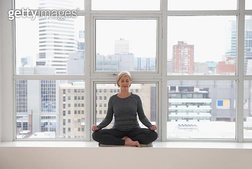 Mature woman doing yoga in loft window - gettyimageskorea