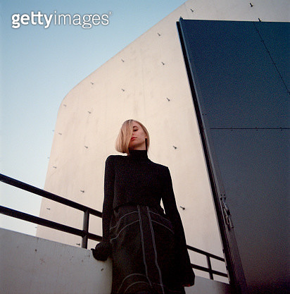 Portrait of young beautiful woman wearing black dress standing near concrete construction and looking at camera. Shot on medium format film camera - gettyimageskorea