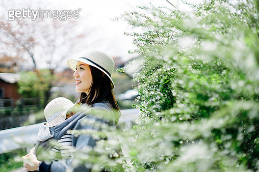 Smiling young Asian mother and little daughter with straw hat on a trip in the nature enjoying the beautiful scenics on a sunny day - gettyimageskorea