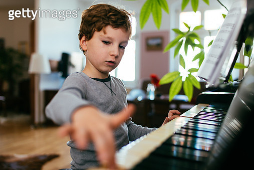 Young boy playing piano at home. - gettyimageskorea