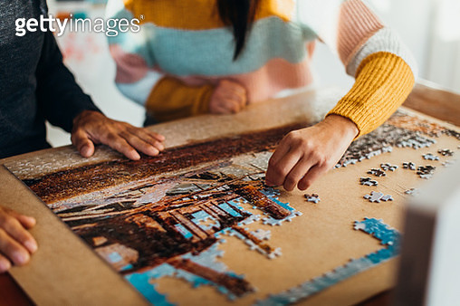 Close up shot of the hands of a couple doing a jigsaw puzzle in their kitchen, shot from in front - gettyimageskorea