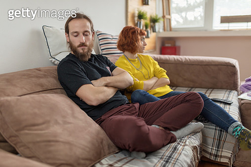 Young couple feeling distant and separated after quarrel at home. - gettyimageskorea