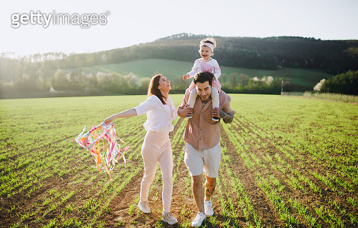 Happy young family with small toddler girl on a walk in spring nature. - gettyimageskorea
