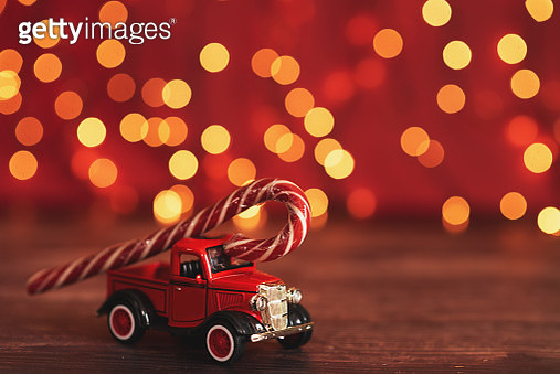 red toy car carries a sugar candy cane on the background of lights - gettyimageskorea