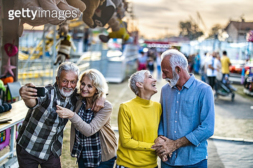 Group of happy seniors having fun while spending a day at amusement park. Two of them are talking while other two are taking a selfie. - gettyimageskorea