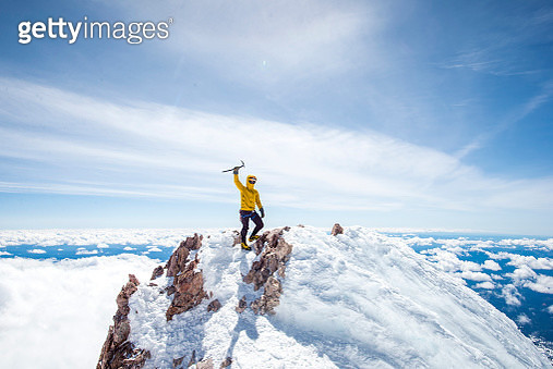 Adventurous mountain climber rising ice pick in victory pose at summit of Mt Shasta, California, USA - gettyimageskorea