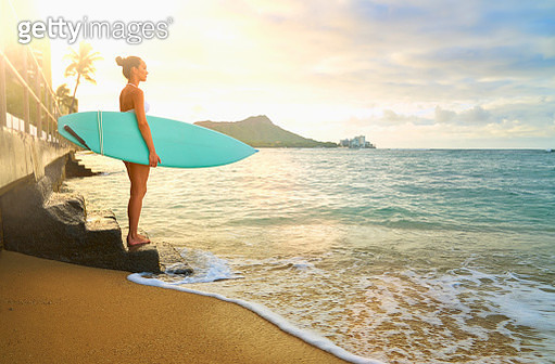 Pacific Islander woman holding surfboard on staircase at ocean - gettyimageskorea