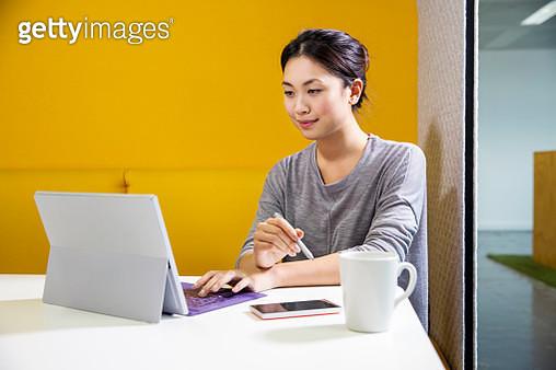 Female digital designer at office desk using laptop - gettyimageskorea