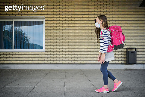 Girl wearing mask and schoolbag walking along building - gettyimageskorea