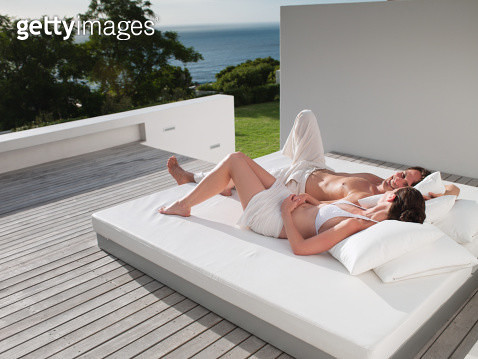 Man and woman lying down on bed outdoors  - gettyimageskorea
