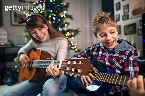 Brother and sister are having fun playing and singing carols together. Kids are playing two guitars.Nikon D850 - gettyimageskorea