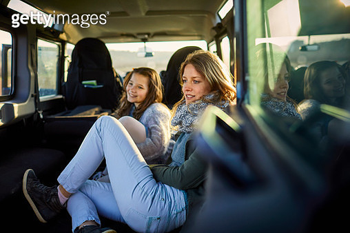 Smiling mother and daughter sitting in an off-road vehicle - gettyimageskorea