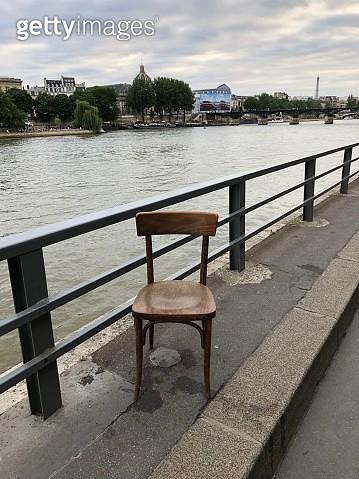 An empty wooden chair along the Seine river. - gettyimageskorea