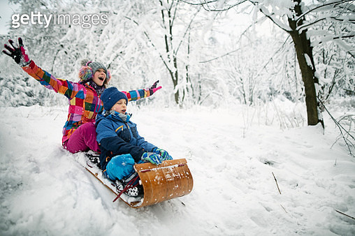 Brother and sister  sledding in winter. - gettyimageskorea