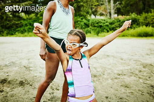 Young girl wearing goggles with arms raised playing at beach on summer afternoon - gettyimageskorea