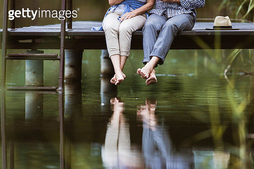 Unrecognizable couple sitting on a jetty at lake while their reflection is seen in water. Copy space. - gettyimageskorea