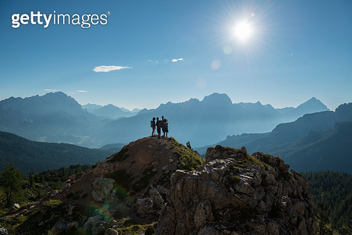 Italy, Friends standing om mountain top in the Dolomites, looking at view - gettyimageskorea