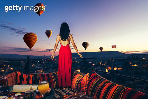 Beautiful asian woman watching colorful hot air balloons flying over the valley at Cappadocia, Turkey.Turkey Cappadocia fairytale scenery of mountains.. Turkey Cappadocia fairytale scenery of mountains. - gettyimageskorea