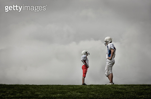 Two people facing each other, one very tall football player, and one much shorter person looking up, hands on hips.  - gettyimageskorea