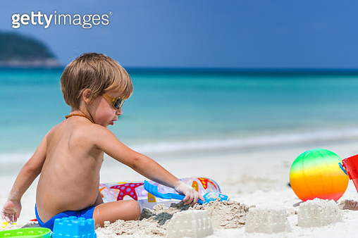 Small boy sitting in sand at the beach and playing with beach toys in summer day. Copy space. - gettyimageskorea