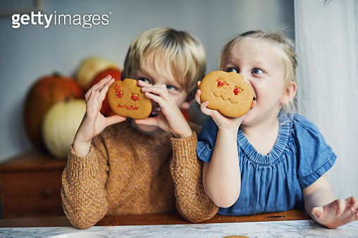 Children decorating pumpkin shaped biscuits together - gettyimageskorea