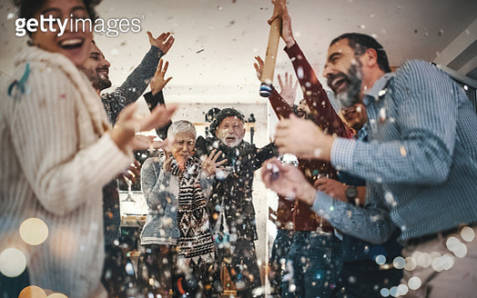 Closeup of group of mixed age people having New year's party at home. They are having champagne, lighting up some fire sparklers and popping confetti. There are two women and five men enjoying this party. - gettyimageskorea