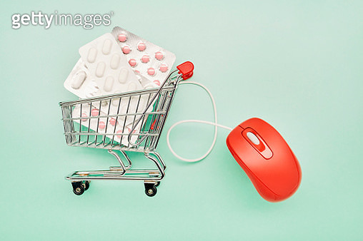 Still life of a small shopping cart with pills and red computer mouse on turquoise background - gettyimageskorea